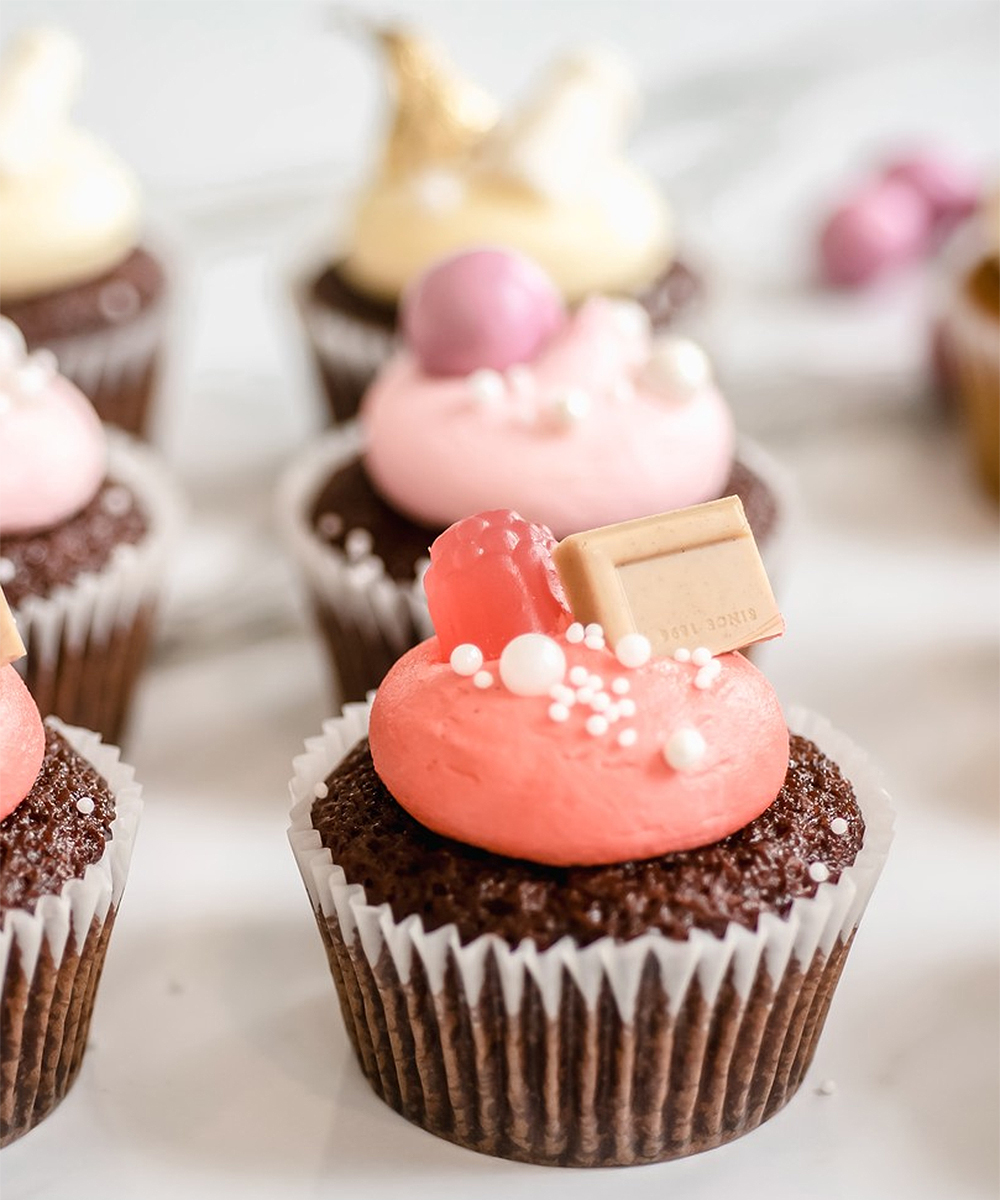 A selection of pretty cupcakes, including a pink one in the front, sit on a marble table..