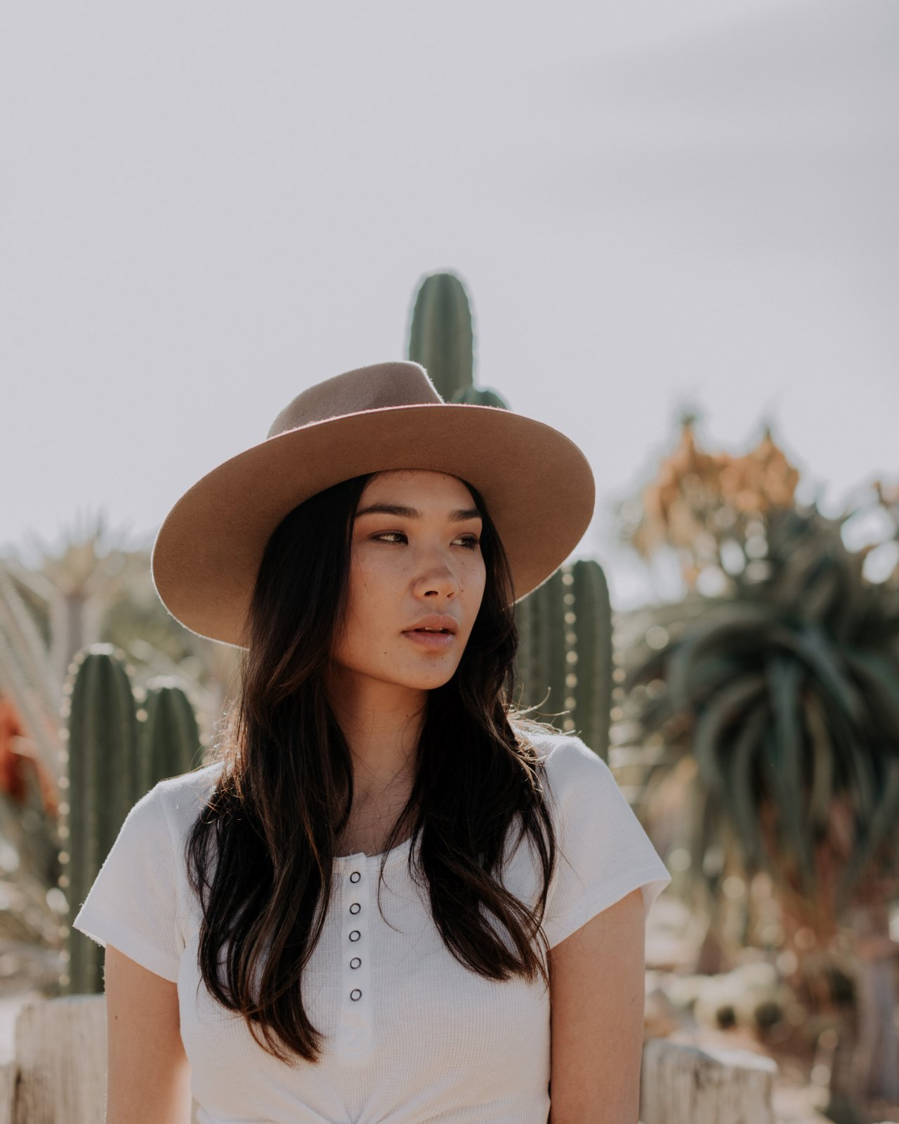 A woman stands in the desert wearing a wool hat.