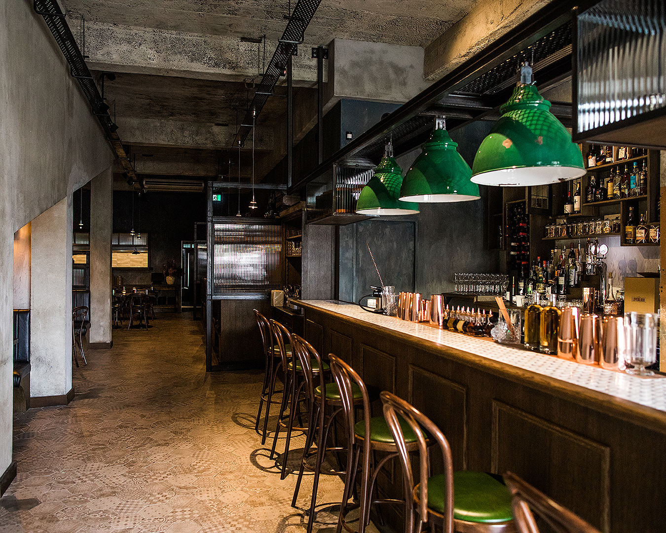 The interior at V.T Station shows green accents and a lovely looking bar.
