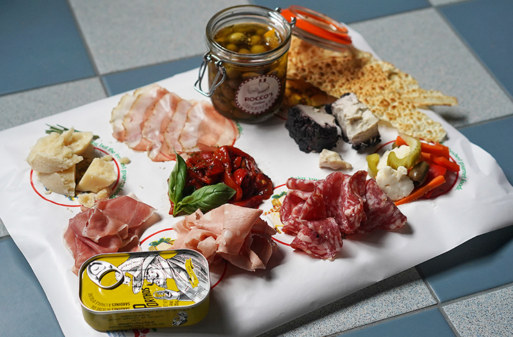 Rocco's antipasti platter stacked with cured meats, olives, cheeses and crips.