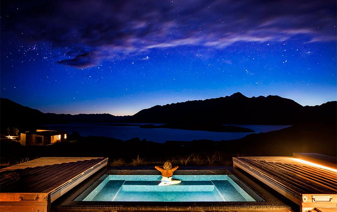 A woman relaxes in a spa under the stars at Aro Ha retreat.
