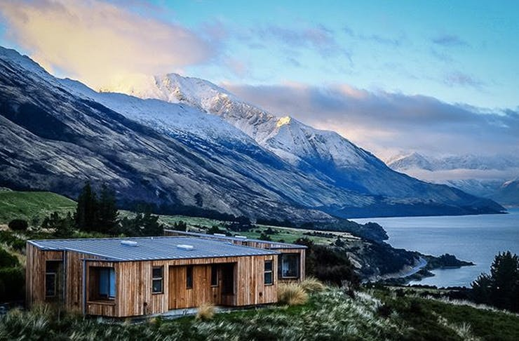 A view of Aro Ha retreat with a cosy looking cabin in the foreground and stunning white-capped mountains behind.