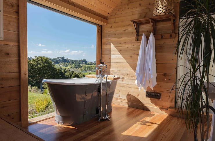 A gorgeous wooden bathroom looking out on scenery.