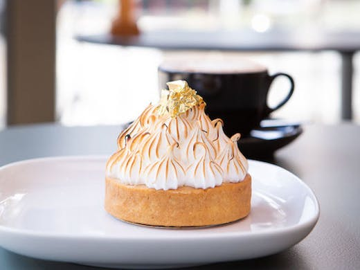 A lemon meringue pie sits atop a white plate