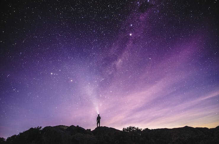 A man stands on a rock in the Australian Outback beneath a canopy of stars.