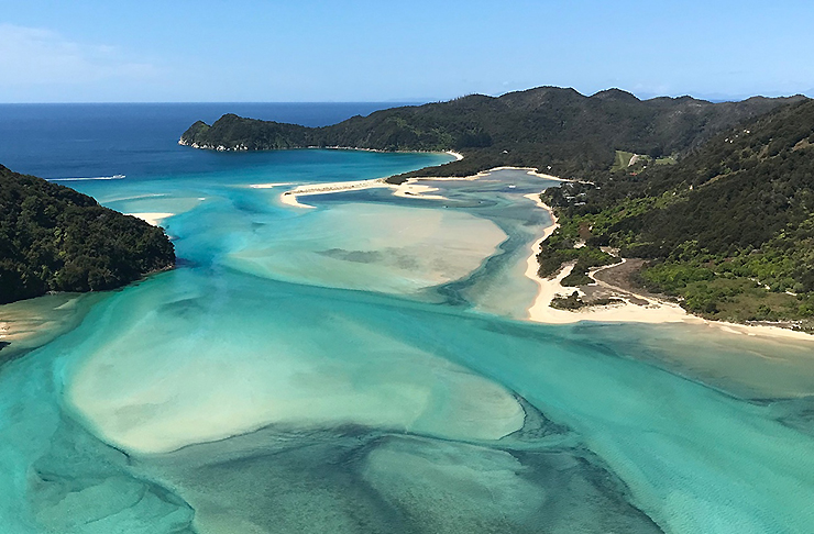 Beautiful blue sea and beaches shows Awaroa Bay from above