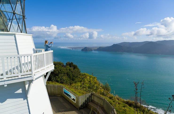 Girl at a lighthouse in Awhitu Peninsula Auckland taking a picture of the view
