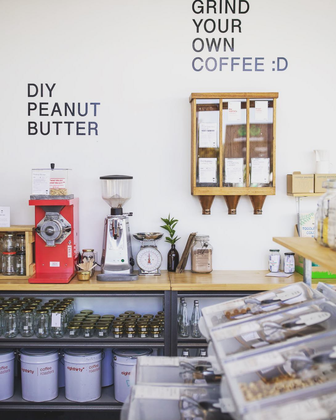 A wall filled with bulk bin goodies including DIY peanut butter and grind-your-own coffee.