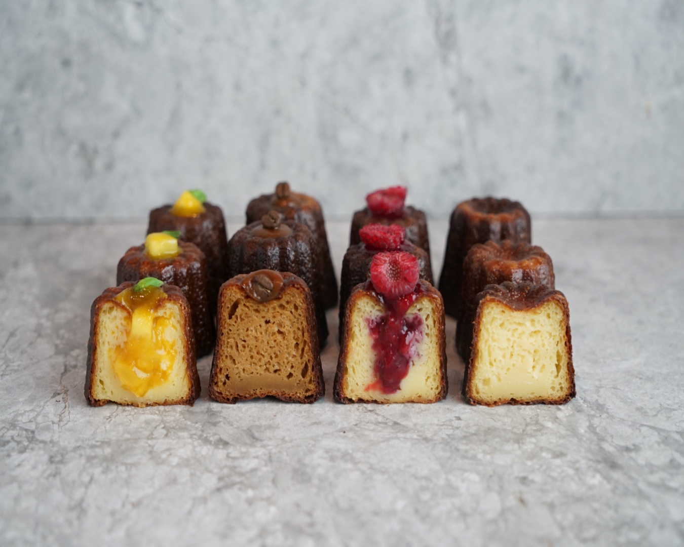 Four cross-sections of canele pastries - lemon curd, raspberry, plain and ginger - on a marble bench