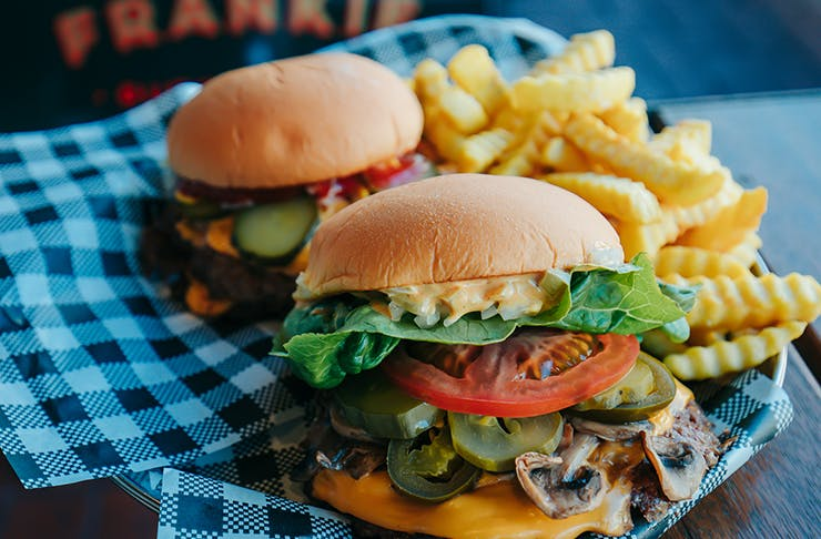 Two of Melbourne's best burgers with stacked toppings and fries on a checkered cloth