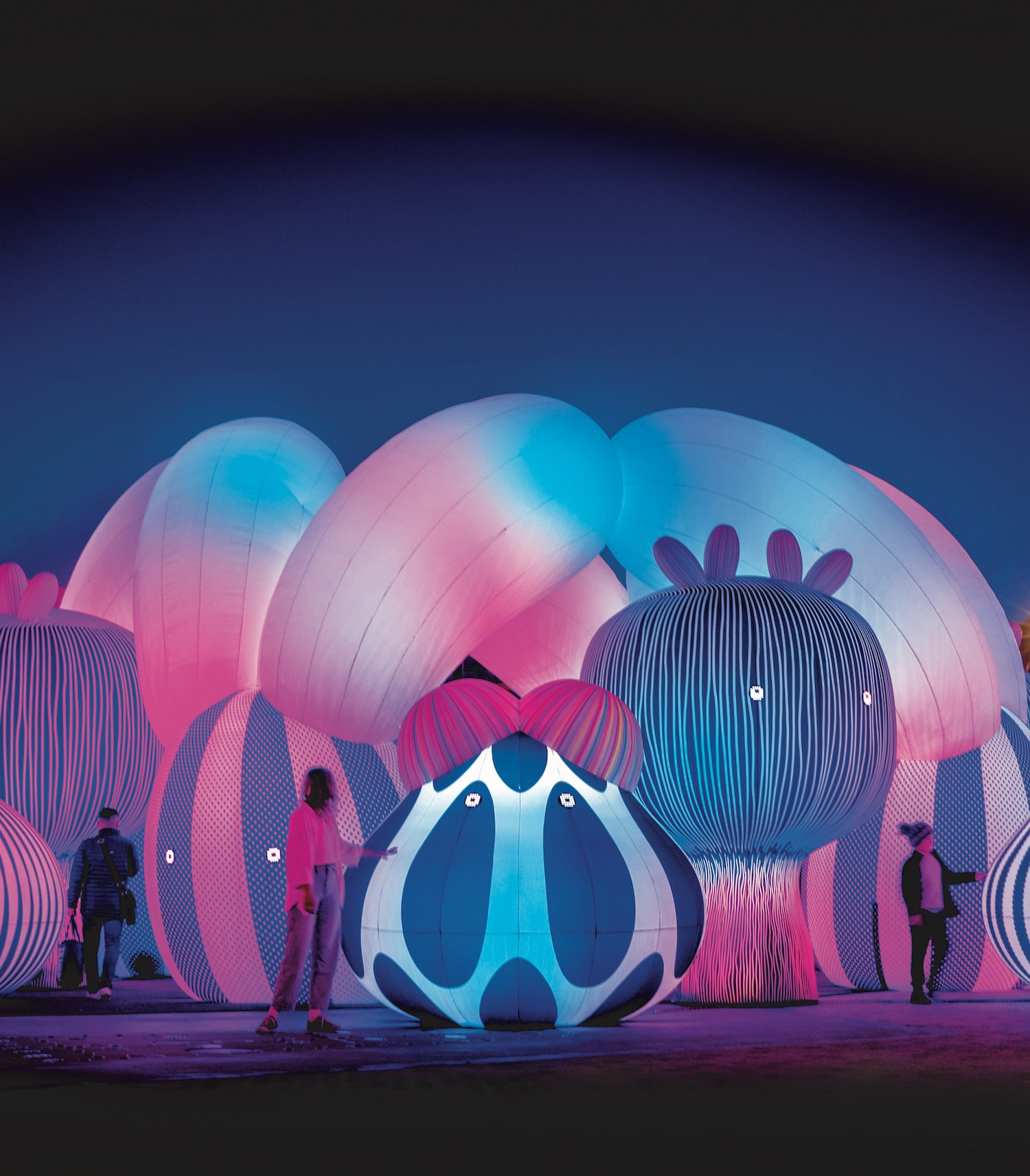 People wander through a huge colourful, inflated installation.