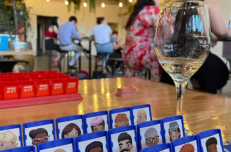 A table of Guess Who with a wine glass next to it