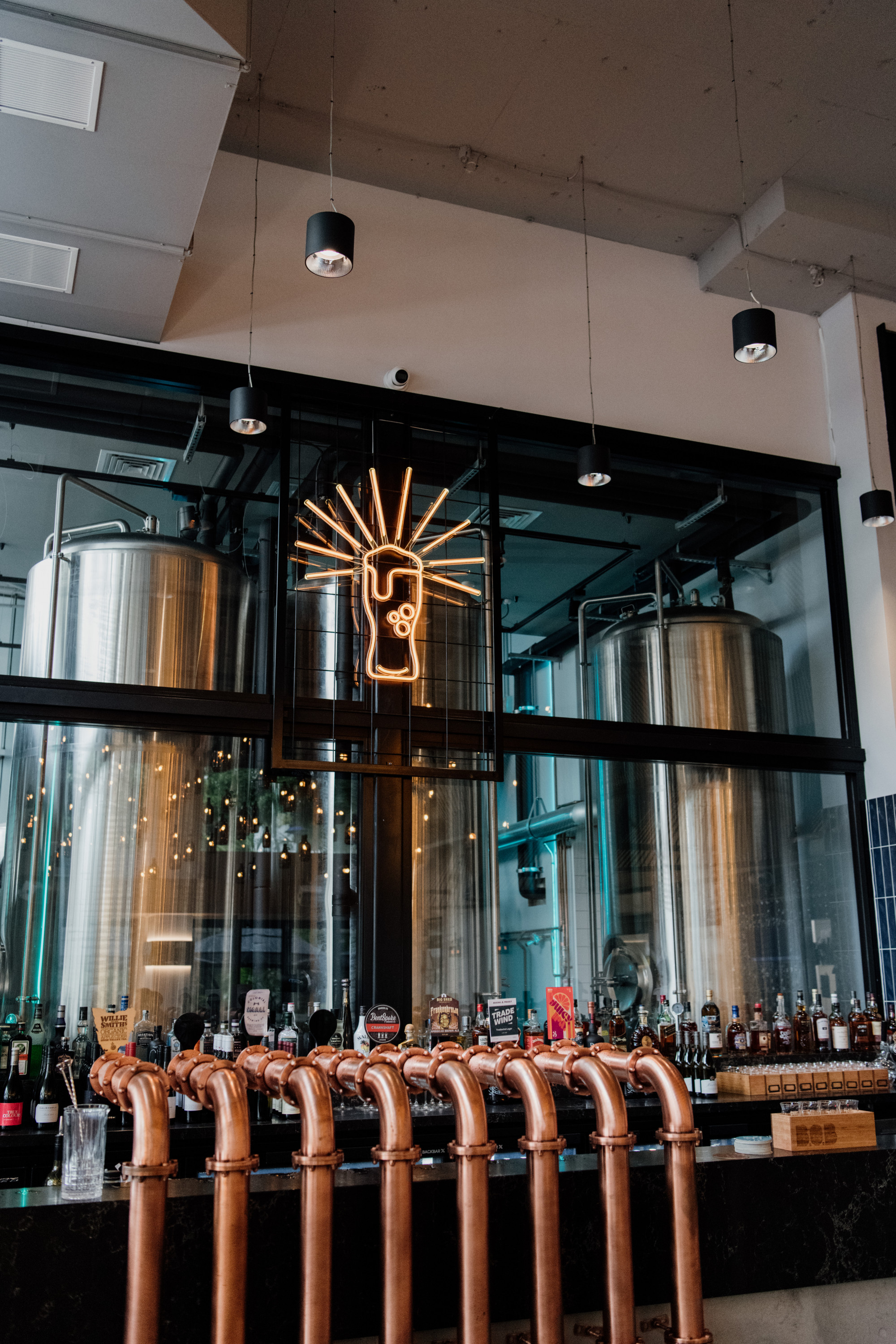 copper beer taps and beer vats in a brewery