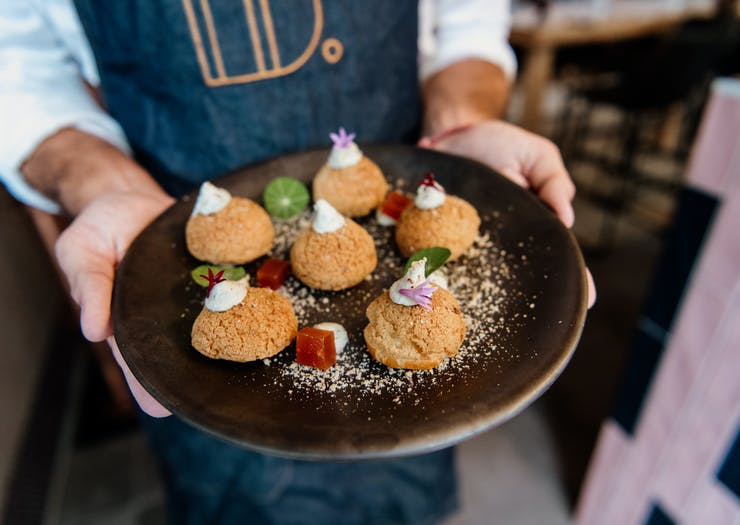 a person with a blue apron holding a dish of savoury profiteroles