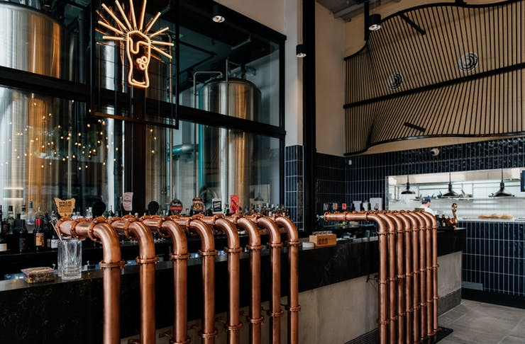 a bar with copper taps and a beer glass neon hanging above it