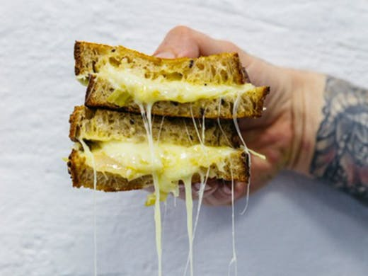 A sandwich being held up with cheese oozing out.
