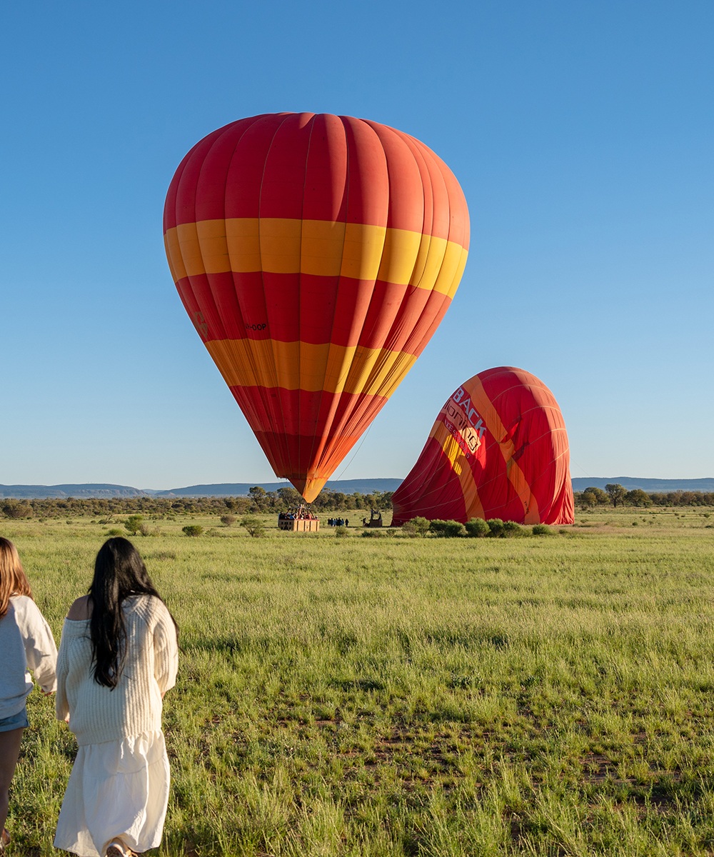 Two women approaching hot air balloons in the outback.