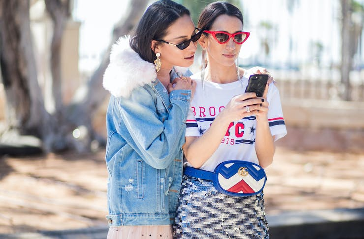 Two women stand close while gazing at a mobile phone.