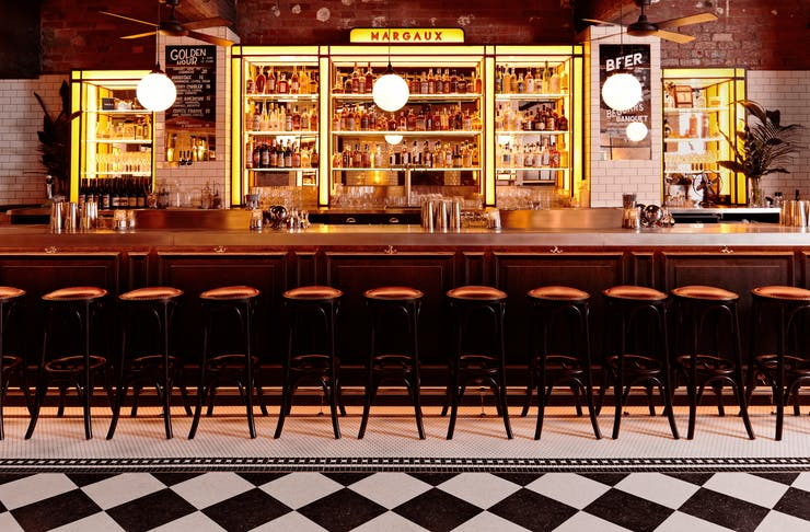 A bar with checkered floors, stools and bottles on a shelf.