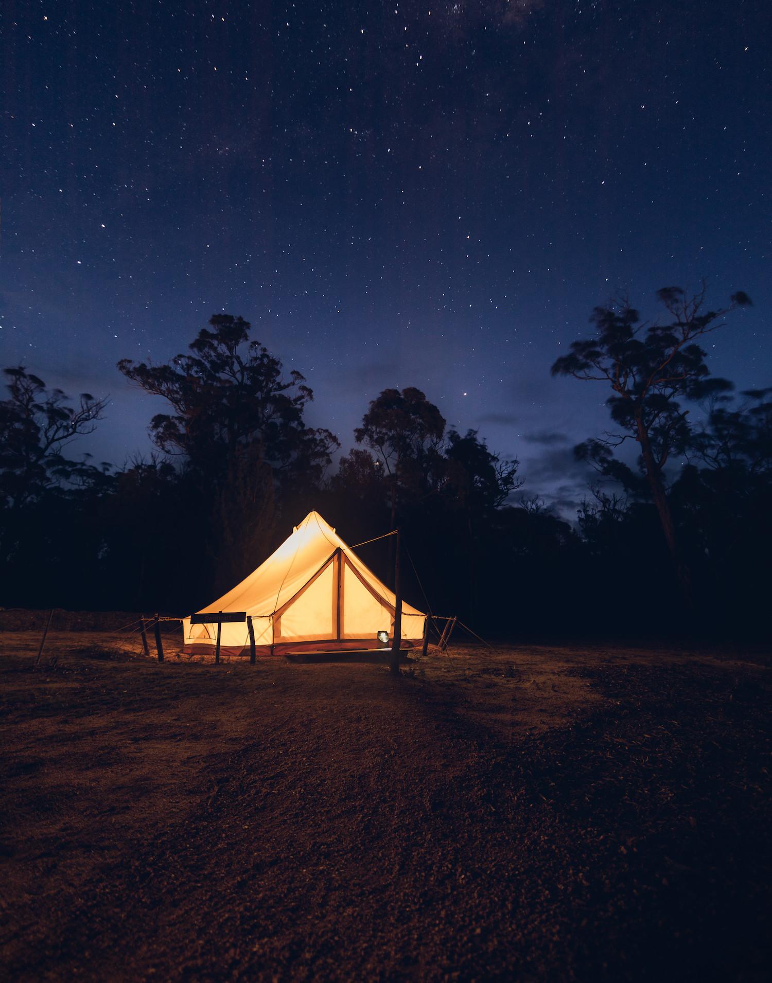 A tent aglow, beneath a blanket of stars in Tasmania.