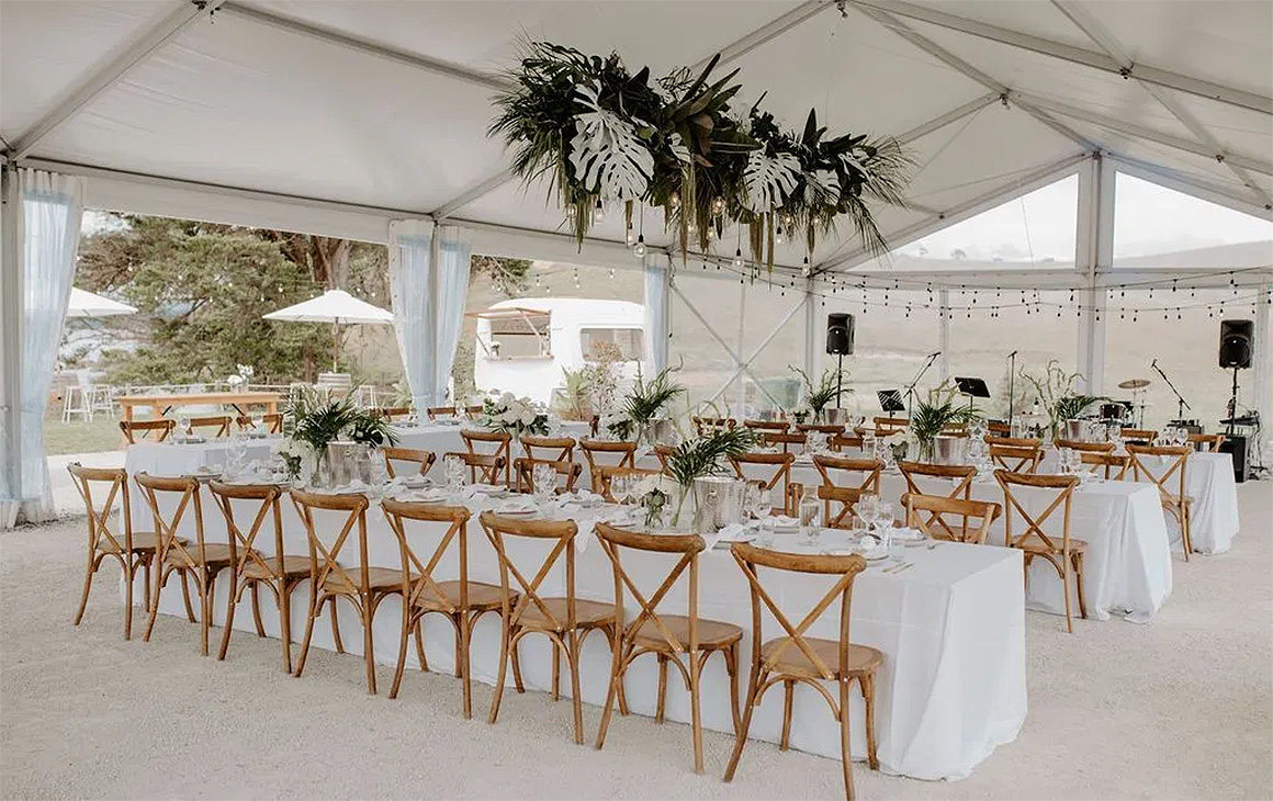 A rustic white room filled with chairs and tables awaiting a wedding banquet.