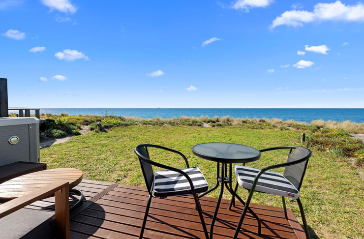 two outdoor chairs and a round glass table sit on a wooden deck, looking out onto lawn and the nearby blue ocean