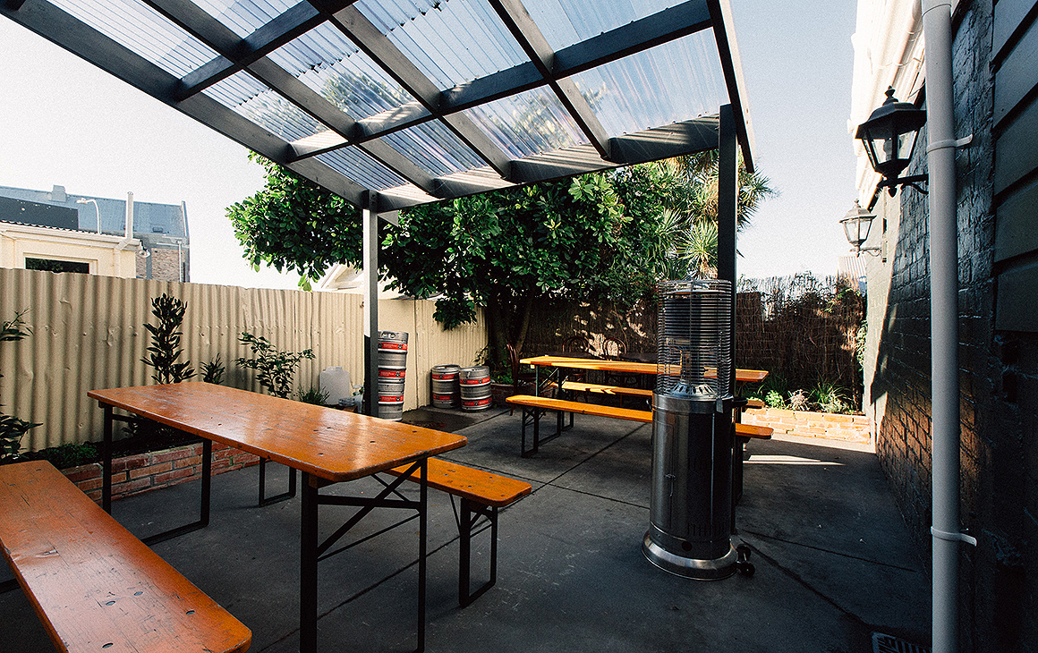 The courtyard outside the back at Beau Wine Bar showing benches and a sunny outlook.