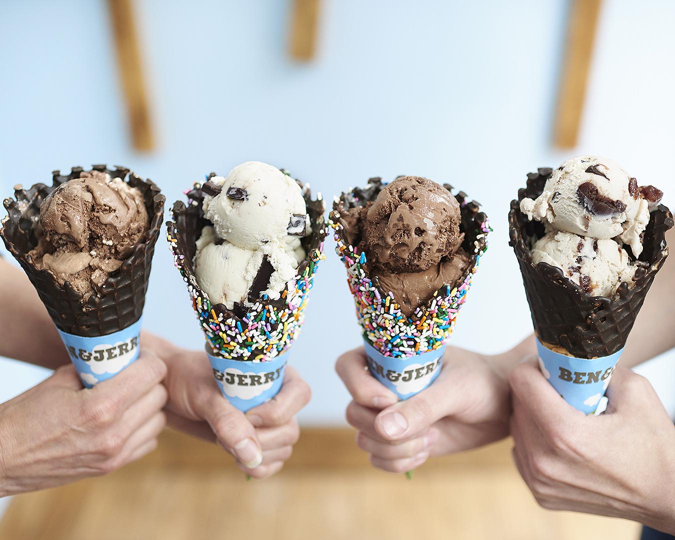 Four cones of delicious Ben & Jerry's ice cream is held aloft.