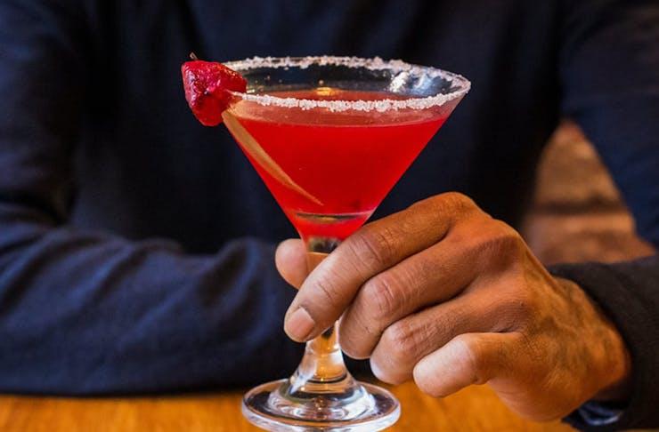 Man holding a pink berry margarita.