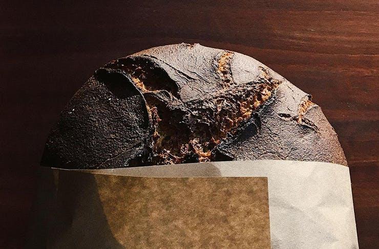 A shot of a loaf of sourdough in a paper bag.