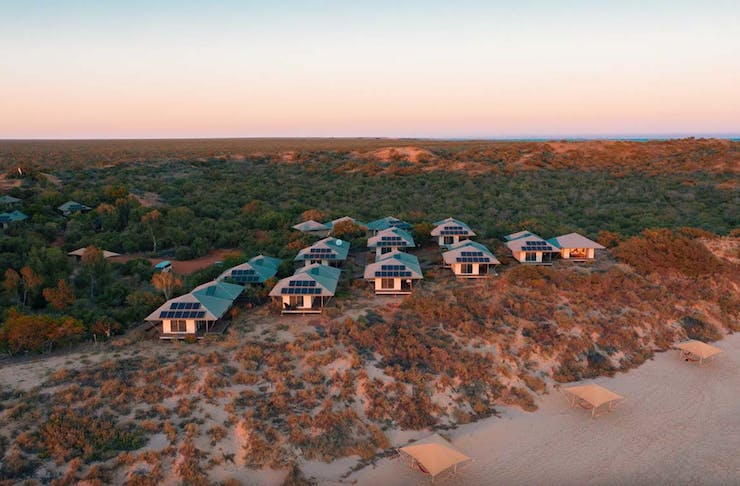a cluster of cabins on the beach at sunset.