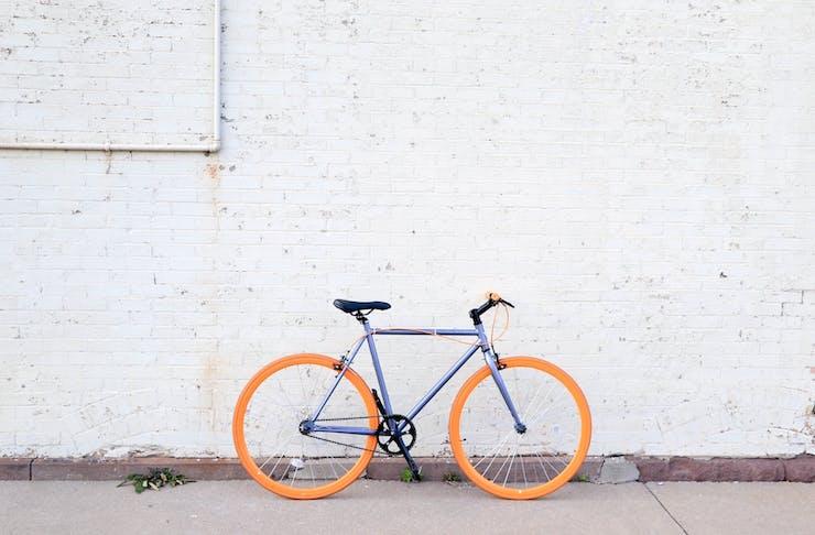 Purple bike with orange wheels against a white brick wall