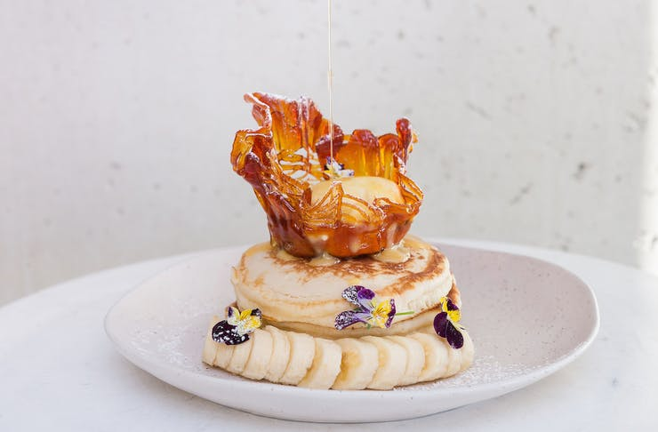 Fluffy pancakes topped with caramel basket and syrup