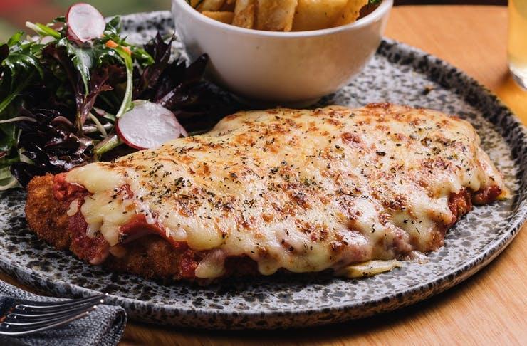 A chicken parmi on a dark plate.