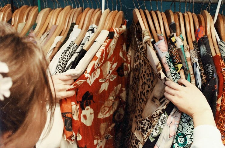 A person looking through racks of vintage clothes at Perth's best markets