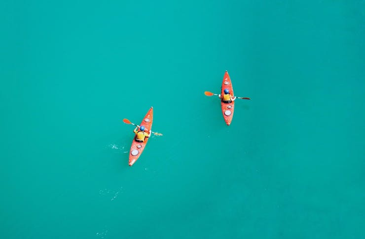 Drone shot of two people kayaking on turquoise blue water