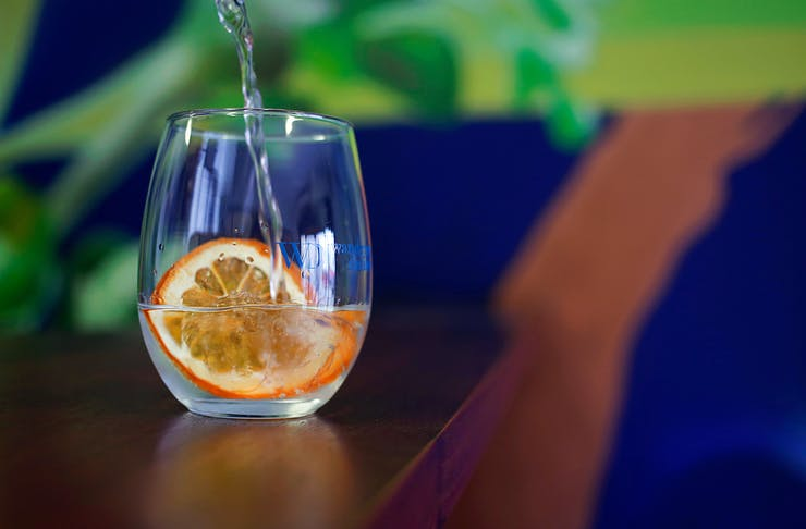 glass of gin with a slice of orange in it