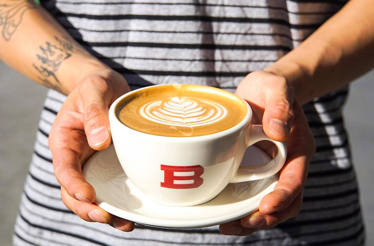 Person with cool forearm tattoos holds a flat white in a white tulip cup with a bright red B