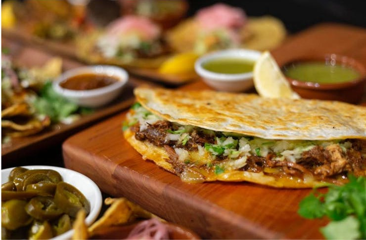A close up shot of Birria tacos with meat, molten cheese and toppings.