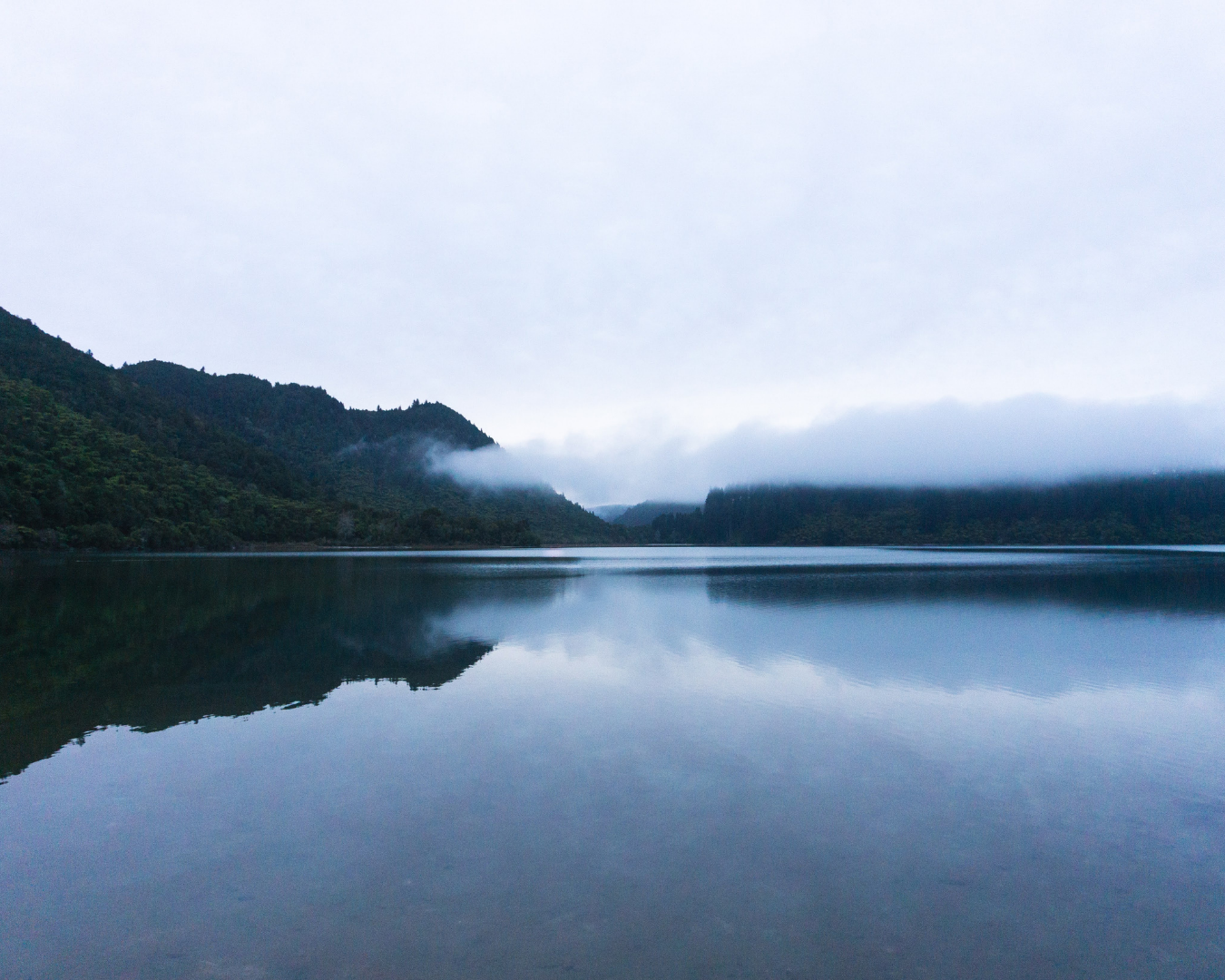 A scenic lake with a view of the clouds descending over the valley