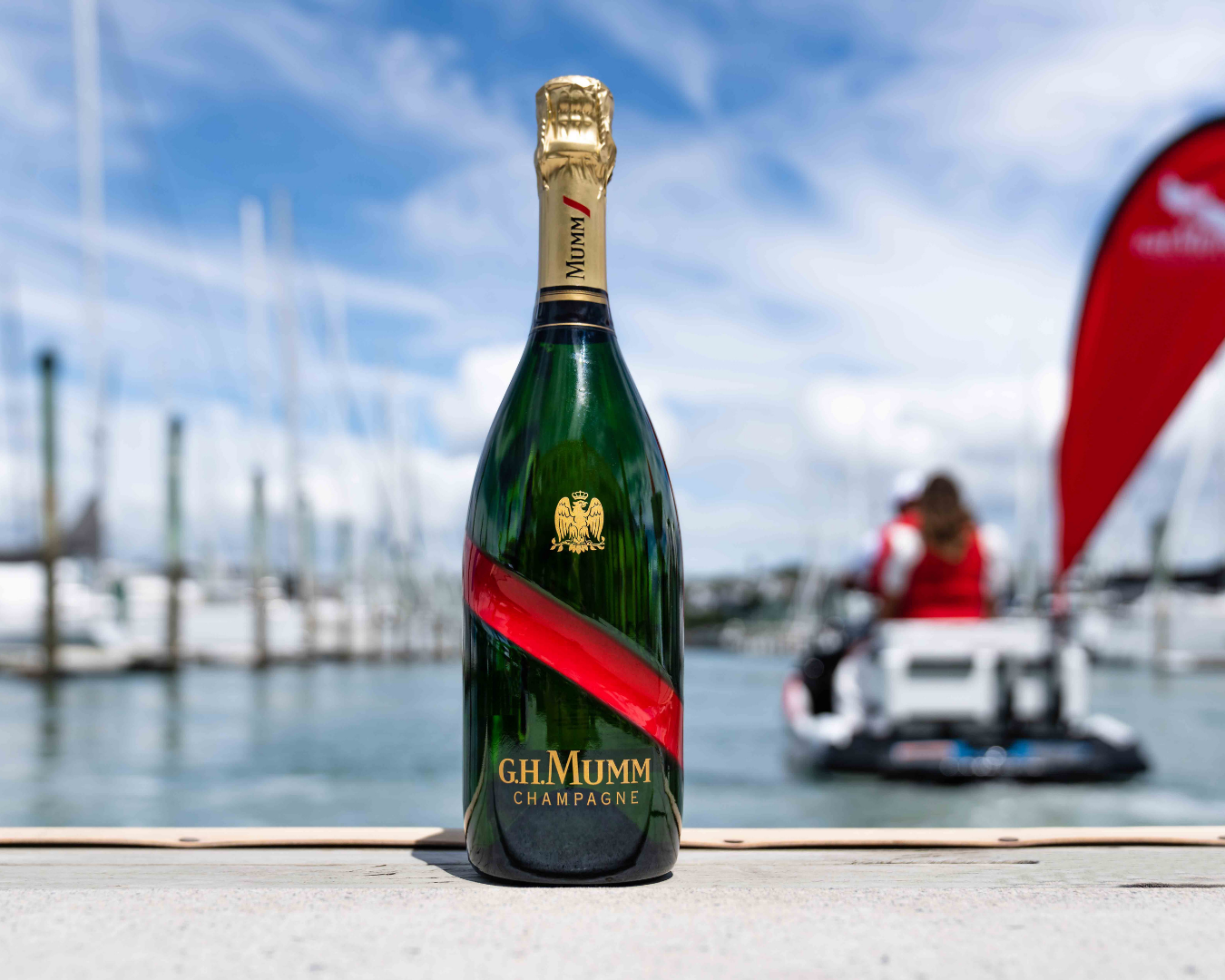 Bottle of G.H Mumm's champagne on the dock with the jet ski in the background