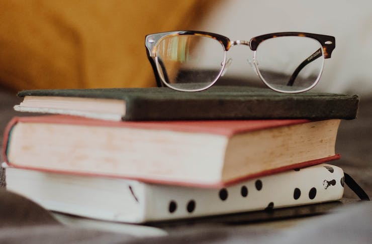 A stack of books with a pair of reading glasses on top