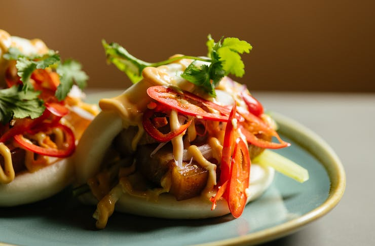 Two bao buns sit on a blue plate. They are filled with pork and coriander slaw.