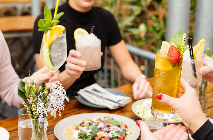 People sit around a table filled with food, they are holding their drinks up as if to cheers