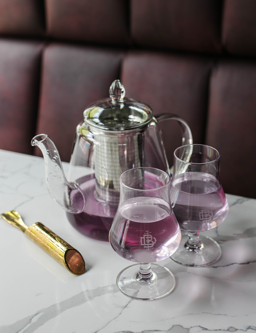 a glass teapot filled with a purple gin cocktail