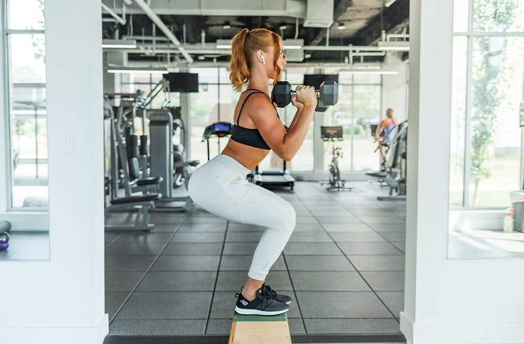 A woman in workout gear squats on a step in a gym.