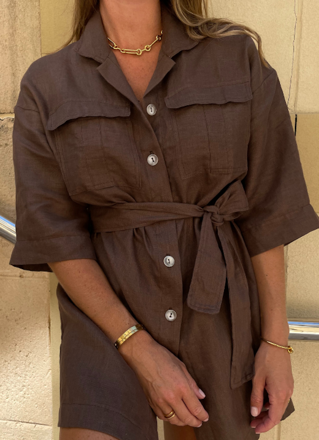 A woman wears a chocolate linen shirt dress paired with gold accessories.