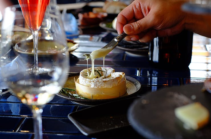 A baked wheel of camembert with honey and rosemary on top with a knife cutting into it and the melted cheese dripping down