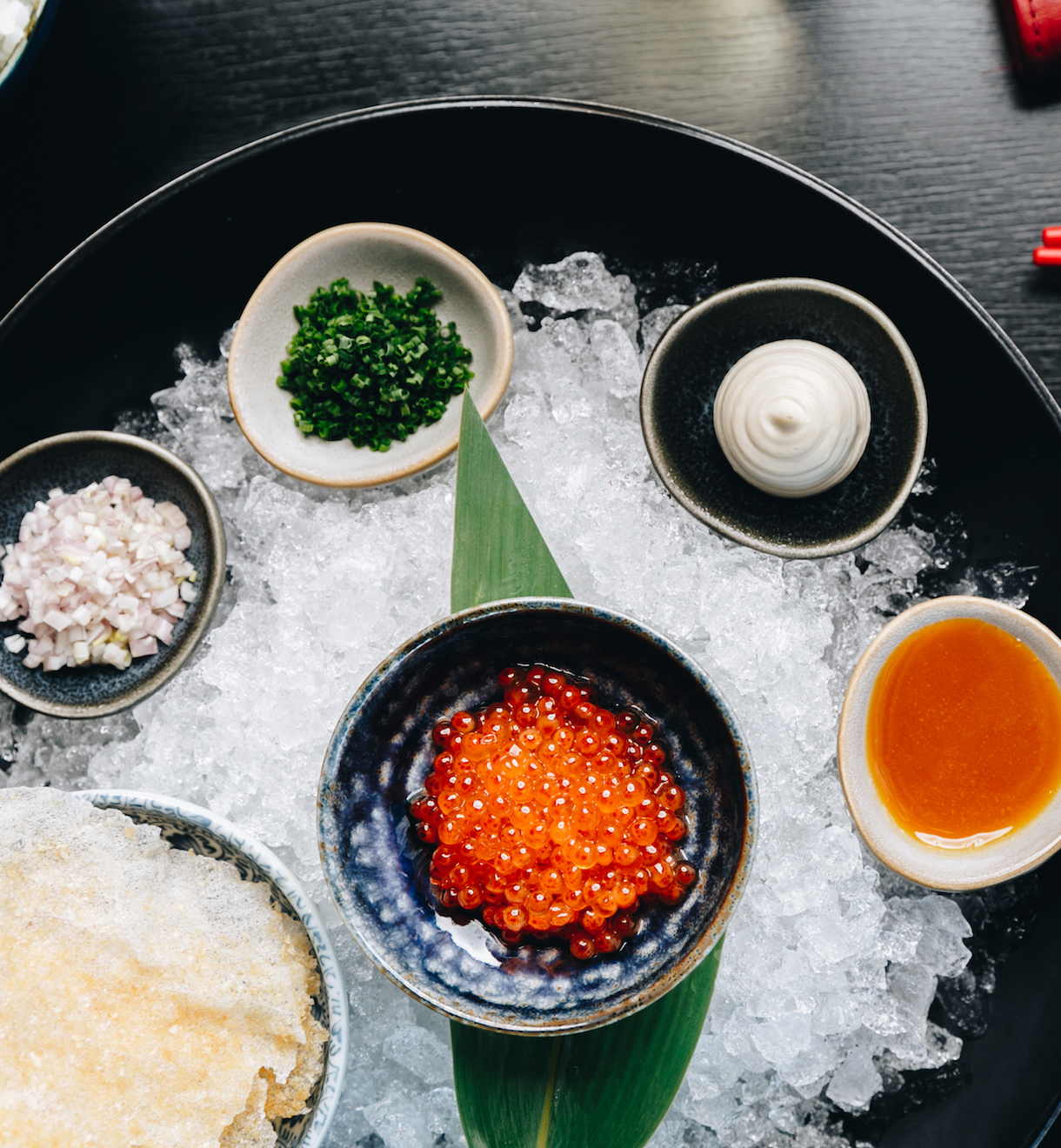 Small bowls of toppings and sauces sits atop a salted plate.