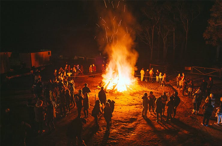 A bonfire with people standing in a circle around the edges